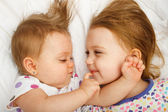 Siblings cuddling in bed — Stock Photo
