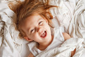 Happy little girl laying in white laundry — Stock Photo