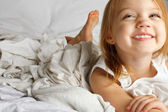 Smiling young girl in white covered bed — Stock Photo