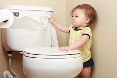 Ornery baby pulling toilet paper off the roll