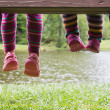 Little feet hanging from a bench at a pond — Stock Photo #50903561