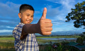 Smiling Kid with thumbs up hand gesture — Stock Photo