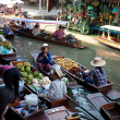 Stock Photo: Bangkok August 2008. Busy sunday morning at Damnoen Saduak floating market. Locals selling fresh produce, cooked food and souvenirs while tourist waits of boats