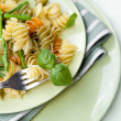 Colorful pasta with asparagus and rocket pesto and basil - Stock Photo