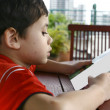 Young boy engrossed while reading a book. — Stock Photo