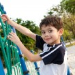 Young boy enjoying the playground climbing activity. - Stock Photo