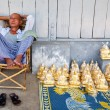 YANGON FEBRUARY 2010. A gold Buddha statues seller taking a nap while waiting for sales at a pavement by the Shwedagon Pagoda on February 7th 2010 — Stock Photo