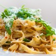 Delicious fettucine pasta with sundried tomato and rocket leaves — Stock Photo
