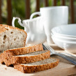 Meal setting with sliced banana bread and serving bowls. — Stock Photo