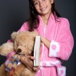 Young girl ready for bed with book and teddy in arm — Stock Photo #12038461