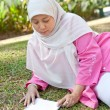 Beautiful mature Muslim woman enjoying the park with a book — Stock Photo