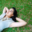Beautiful young female laying on the grass, thinking — Stock Photo
