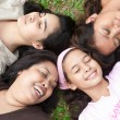 Royalty-Free Stock Photo: Asian moms and their young daughters laying head to head in the park