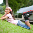 Beautiful young girl resting after rollerblading in the park — Stock Photo #12038518