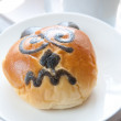 Freshly baked bun with funny bear face - Stock Photo