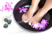 Feminine feet in foot spa bowl with orchids — Stok fotoğraf