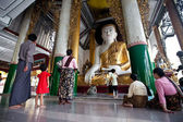 YANGON, MYANMAR - JAN 28: Buddhist devotee praying to statue of Buddha — Stock Photo
