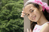 Beautiful young girl of mix parentage on a garden terrace — Stock Photo