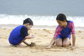 Sister and brother at a tropical beach enjoying the sand together. — Stock Photo