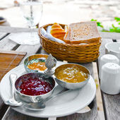 Breakfast on the terrace with toast, buns, croissant and assorted preserve. — Stock Photo
