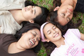 Asian moms and their young daughters laying head to head in the park — Stock Photo