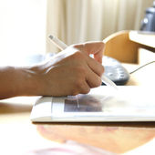 Hand holding stylus pen while working on tablet attached to computer. — Stock Photo