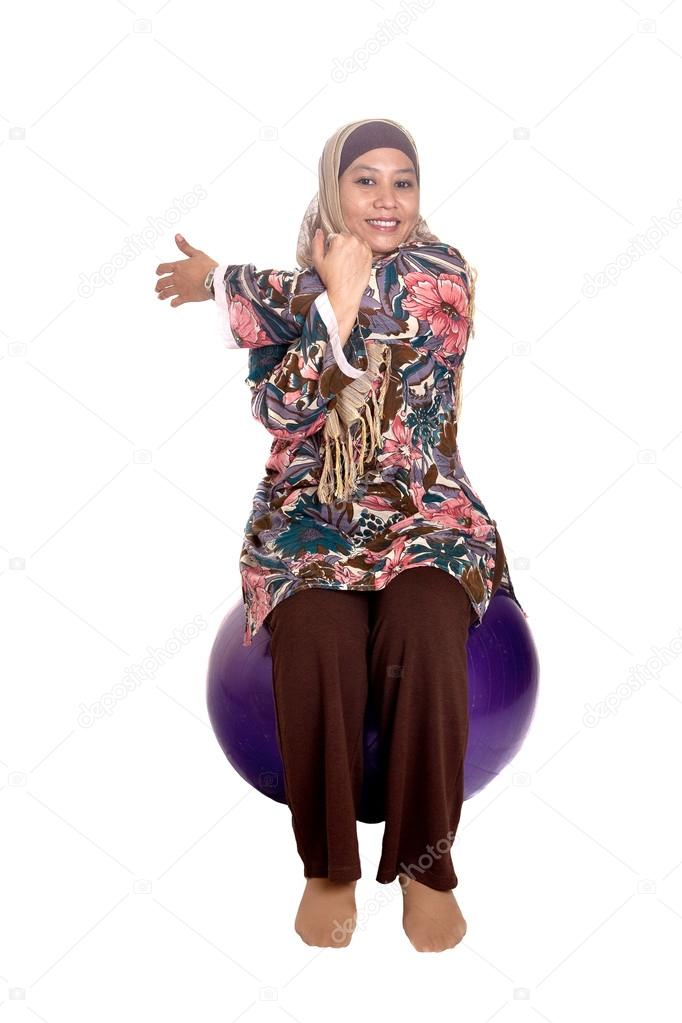 Muslim woman on fit ball while stretching her tricep as part of healthy lifestyle concept — Stock Photo #12038420