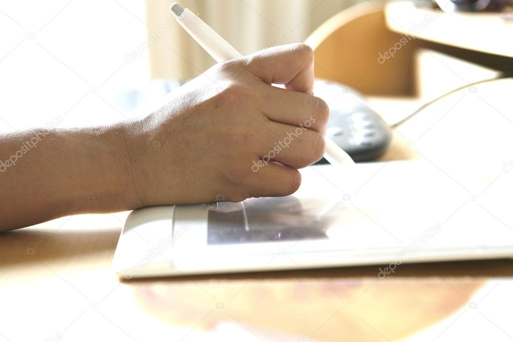 Hand holding stylus pen while working on tablet attached to computer.  — Stock Photo #12038566