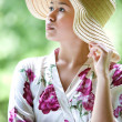 Beautiful Asian girl with wide brim straw hat in the park — Stock Photo