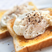 Two delicious poached egg on toast with freshly cracked black pepper — Stock Photo