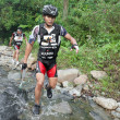 SABAH, MALAYSIA - APRIL 2ND. A racer from a participating team makes his way along a river in the early morning race for the Sabah Adventure Challenge, April 2nd, 2010, Sabah, Malaysia. - Stock Photo
