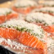 Fresh salmon steak with fresh basil pesto and sprinkling of parmesan — Stock Photo