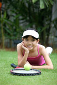 Young girl with a tennis racket and tennis ball in the garden. — Stock Photo