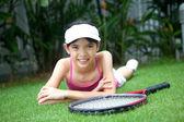 молодая девушка с теннисной ракеткой в саду. — Стоковое фото