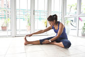Asian fitness woman stretching her hamstring while being on the floor — Stock Photo