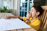 Young boy yawning as he does his homework — Stock Photo