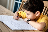 Young boy doing his homework at home. — Stock Photo