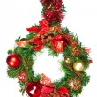 A hanging christmas wreath in green and red with colorful baubles - Stock Photo