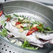 Fresh sea bass fish with oriental ingredients ready for steaming. — Stock Photo