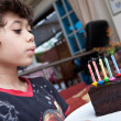 Young boy blowing out candles on a slice of chocolate cake - Stock Photo