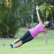 Young fitness woman doing stretching exercise outdoor - Stock Photo