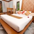 Beautiful kingsize bed in a tropical hotel bedroom. - Stock Photo