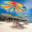 Idyllic tropical island getaway with sunbeds and parasols on white sandy beach - Stock Photo