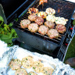 Sizzling burgers and chicken kebabs on hot barbecue outdoor. - Stock Photo