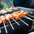 Stock Photo: Sizzling burgers and chicken kebabs on hot barbecue outdoor.