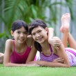 Two beautiful Chinese sisters in outdoor garden — Stock Photo #19828269