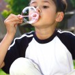 Young boy having fun playing bubbles in the garden — Stock Photo
