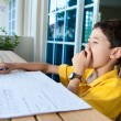 Young boy yawning and getting tired while doing his homework — Stock Photo