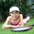 Young girl with a tennis racket in the garden. — Stock Photo