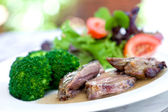 Roast lamb with gravy served with broccoli and salad — Stock Photo